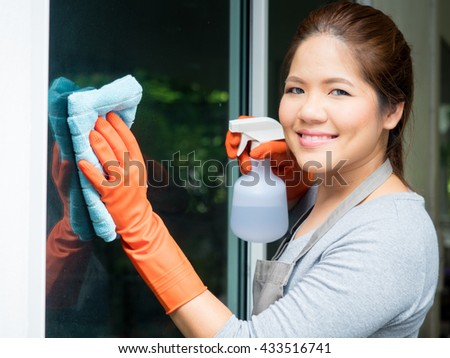 asian woman cleaning glass - stock photo
