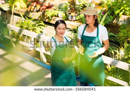 Asian woman consulting man about new sorts of plants in the greenhouse - stock photo