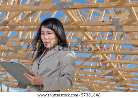 Asian Woman Contractor looking at job sheet on location - stock photo