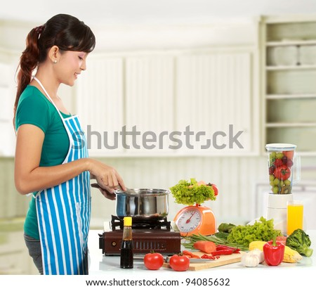 asian woman cooking in the kitchen - stock photo