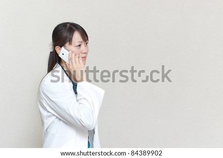 Asian woman doctor talking with smart phone - stock photo