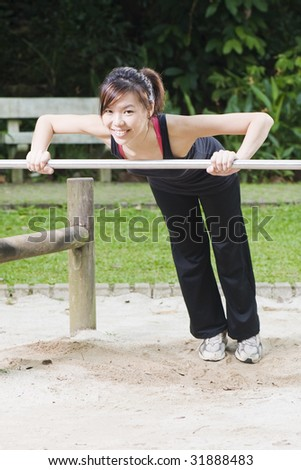asian woman doing push up on a low bar at a fitness corner - stock photo
