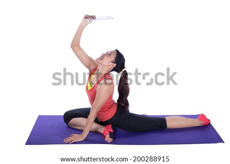 asian woman doing yoga with tablet against white background - stock photo