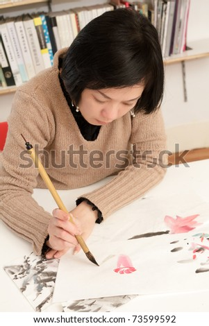 Asian woman drawing Chinese traditional ink painting at home.