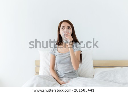 Asian woman drinking a glass of water at living room - stock photo
