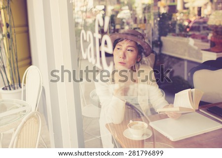 Asian woman drinking coffee and using computer in cafe. Photo filter effect. Selective focused - stock photo