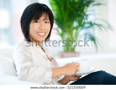 Asian woman drinking coffee at home.