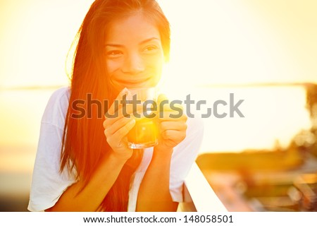 Asian woman drinking coffee in sun sitting outdoor in sunshine light enjoying her morning coffee. Smiling happy multiracial female Asian Chinese / Caucasian model in her 20s. - stock photo