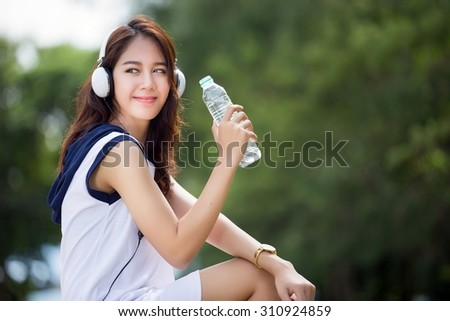 Asian woman drinking water after exercise at the park. During the summer - stock photo