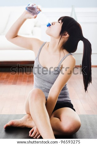 Asian woman drinking water from a bottle after a workout at home. - stock photo