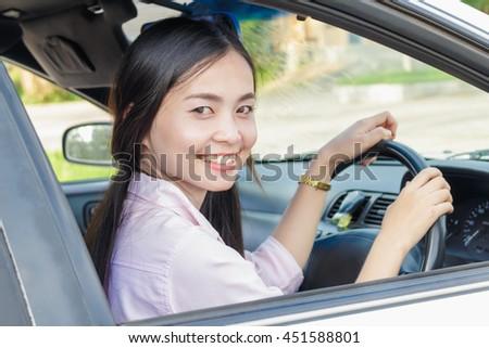 Asian woman driving a car - stock photo