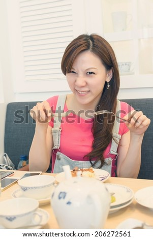 Asian woman eat lunch with funny face. - stock photo