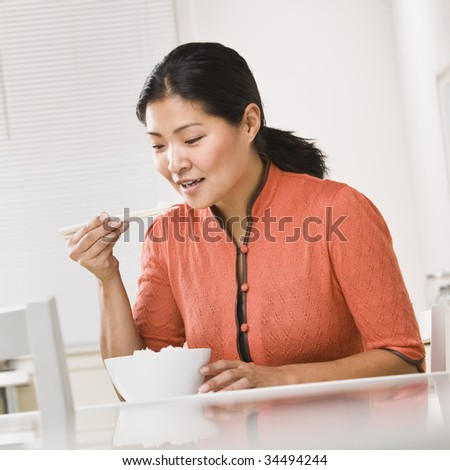 Asian woman eating a bowl of rice with chopsticks. Square - stock photo
