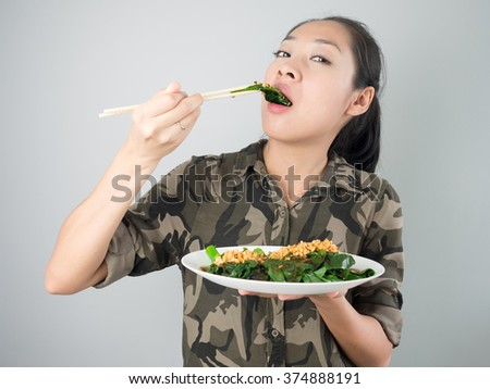 Asian woman eating kale fried in oyster sauce.