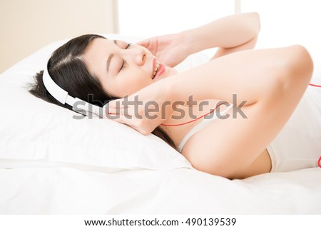 asian woman enjoy music by smart phone with headphones lying on bed. home indoors background