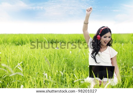 Asian woman enjoying summer by listens to digital music on her laptop outdoor