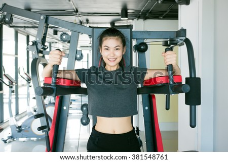 Asian woman exercising on Shoulder press machine at gym - stock photo