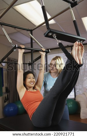 Asian woman exercising with personal trainer - stock photo