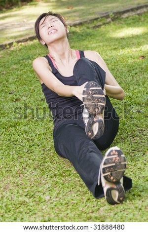 asian woman experiencing leg cramp after a physical activity - stock photo