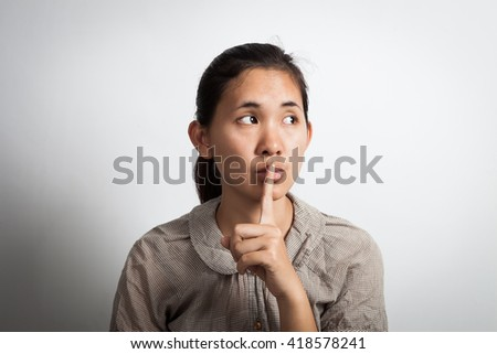 Asian woman finger on her lips. silence gesture looking at right side. - stock photo