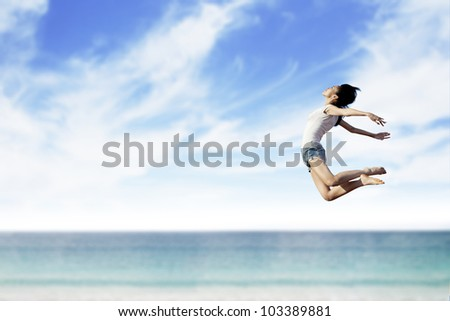 Asian woman flying at the beach. Copy space available for your own text