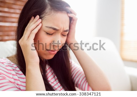 Asian woman getting headache on couch at home in the living room
