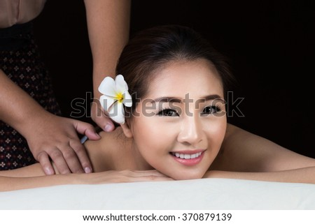 Asian woman getting thai herbal compress massage in spa.She is very relaxed