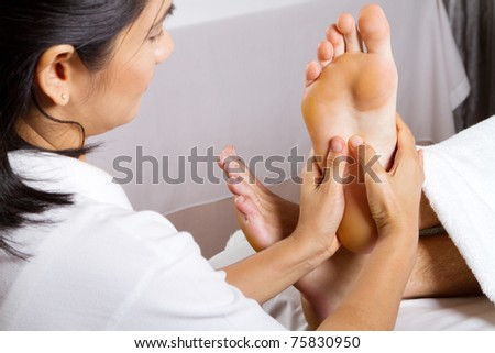 asian woman giving professional foot massage