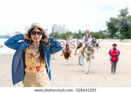 Asian woman hands touch hat at Hua Hin beach Thailand in summer concept