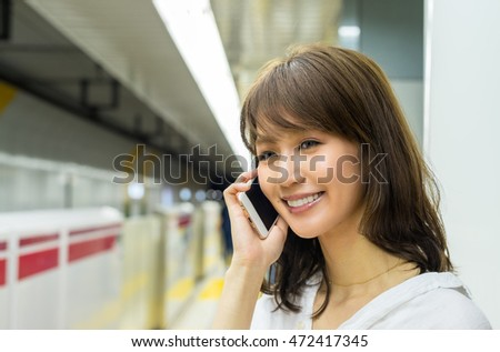 Asian woman happy using her smartphone inside subway station.