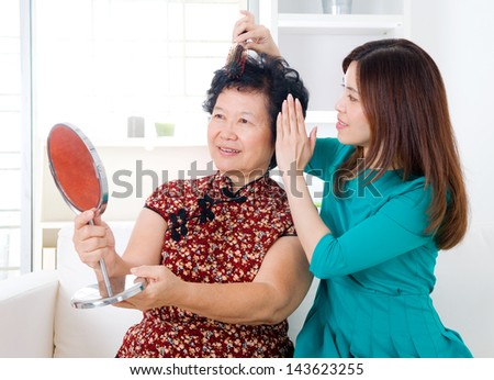 Asian woman helping mom to comb her hair - stock photo