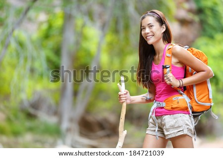 Asian woman hiker hiking in forest standing with backpack and wooden hike stick smiling happy living healthy active outdoor lifestyle. Beautiful young mixed race Asian Caucasian female model. - stock photo