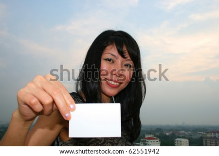 Asian woman holding a business card. - stock photo