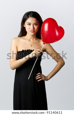 Asian Woman holding a gift for Valentines Day - stock photo