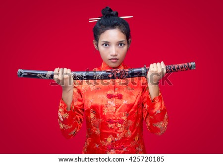 Asian woman holding a sword. Asian woman in traditional costume shows sword. Woman in red offering sword.
