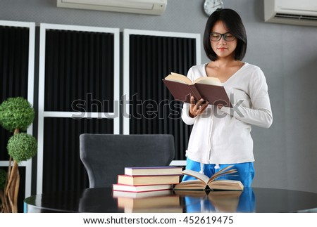 Asian woman holding and open a book in the library.