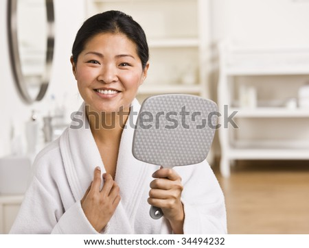 Asian woman holding mirror, wearing robe and smiling at camera.Horizontal. - stock photo