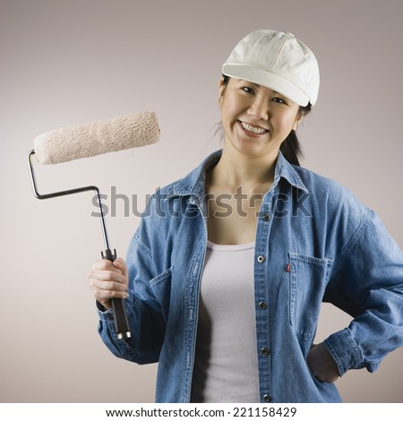 Asian woman holding paint roller - stock photo