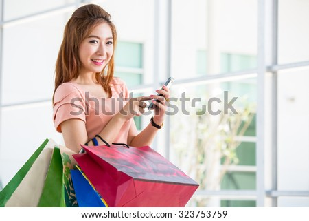 Asian woman holding shopping bag and use smart phone in Department store