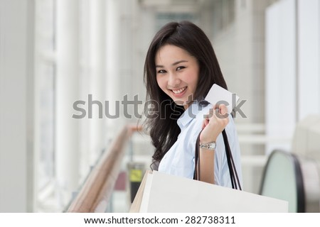 Asian woman holding shopping bags and a card - stock photo