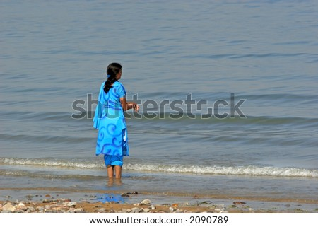 Asian woman in a blue silk sari at the beach paddling in the sea and looking into the distance.