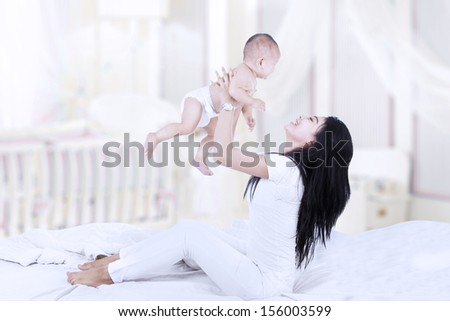 Asian woman in bedroom lifting a baby into the air - stock photo