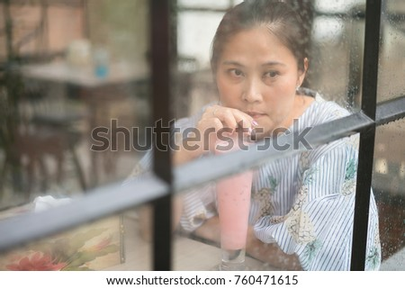 Asian woman in coffee shop sitting at the glass wall on a rainy day and drinking strawberry milk.