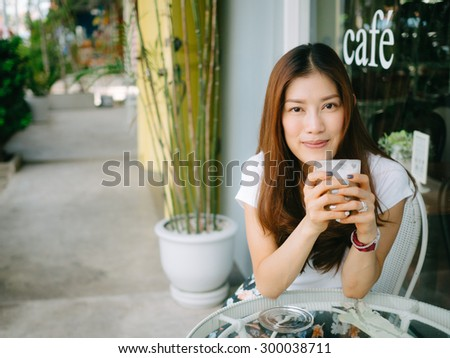 Asian woman in coffee shop vintage color filter tone
