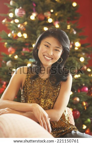 Asian woman in front of Christmas tree - stock photo