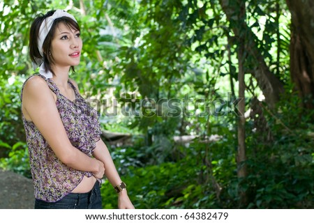 Asian woman in green forest - stock photo