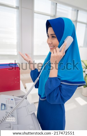 Asian woman in hijab talking on the telephone in the office - stock photo