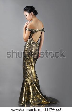 Asian woman in long beautiful golden dress - stock photo