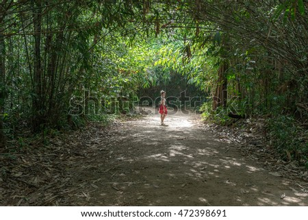 Asian woman in red standing in the trees tunnel in the forest.