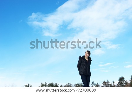 Asian woman in winter fashion, against blue sky